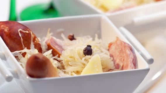 Sauerkraut mit Würstchen- und Kasselerstücken in einer Schale. © picture-alliance / maxppp Foto: Serge Manceau