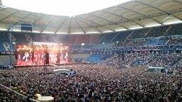 Eine volle Konzerthalle, Udo Lindenberg spielt im Hintergrund auf der Bühne.  © Susanne Schneider Foto: Susanne Schneider