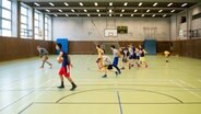Kinder spielen Basketball in einer Sporthalle. © picture alliance / dpa Foto: Felix Zahn