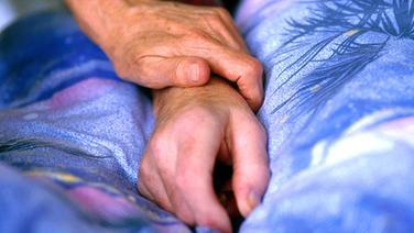 Ein Angehöriger hält dem Sterbenden seine Hand. © epd