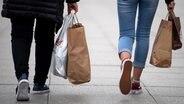 Zwei Menschen gehen mit vollen Einkaufstaschen durch die Stadt. © picture alliance/dpa Foto: Monika Skolimowska