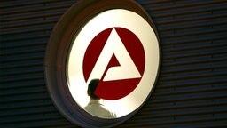 Hinter einem Fenster mit dem Logo der Agentur für Arbeit steht ein Mann im Treppenhaus. © picture-alliance/ dpa Fotograf: Franz-Peter Tschauner