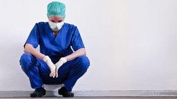 Eine Ärztin in OP-Kleidung lehnt erschöpft an einer Wand © picture alliance/JOKER Foto: Alexander Stein