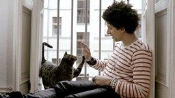 Popsänger Andreas Bourani spielt mit einer Katze. © Universal Music