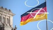 Eine Deutschlandflagge weht hinter einem Wahlkreuz vor dem Bundestag. © fotolia.com Fotograf: pit24, opicobello