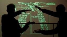 Schatten vor einer Projektion aus Programmiercode © dpa Foto: Axel Heimken
