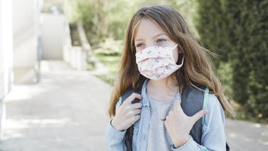 Ein Mädchen mit Schulranzen und Schutzmaske auf dem Schulweg. © panthermedia Foto: Hannes_Eichinger