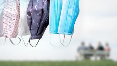 Verschiedene Schutzmasken hängen vor vier Personen, die auf einer Bank am Deich sitzen. (Bildmontage) | COLOURBOX, Photocase