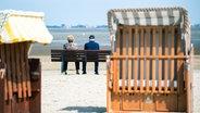 Niedersachsen, Dangast: Ein älteres Pärchen sitzt bei sonnigem Wetter am Strand von Dangast auf einer Bank.  Foto: Mohssen Assanimoghaddam