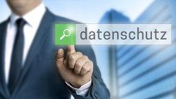 """Ein Mann zeigt auf den Begriff """"Datenschutz"""" auf einem Touchscreen an einer Wand. © Colourbox Foto:  WSF"""