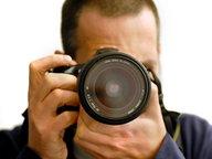 Ein Fotograf mit einer digitalen Spiegelreflexkamera © picture alliance / dpa Themendienst