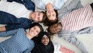 Fünf junge Menschen liegen mit den Köpfen in der Mitte auf dem Fußboden und bilden einen Stern. © picture-alliance / Zoona