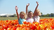 Three girls with raised hands in tulip field © picture alliance/VISIONSPICTURES