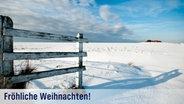 Eine verschneite, sonnige, friesische Weidelandschaft mit Holzgatter und einer kleinen Häusergruppe am Horizont. © fotolia.com Fotograf: Matthias Krüttgen