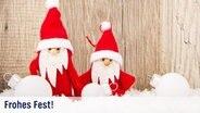 Zwei kleine gebastelte Weihnachtsmänner hinter Schneepulver und vor einer Holzwand. © fotolia.com Fotograf: Tom