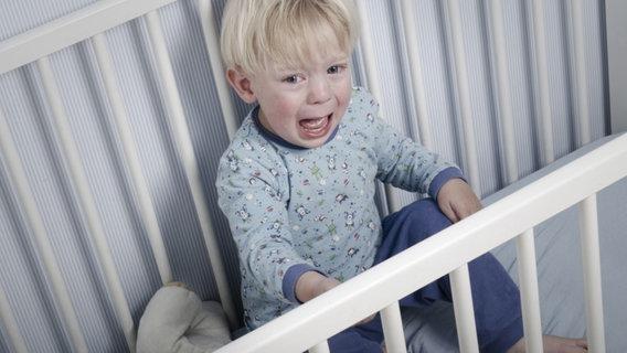Kleinkind sitzt weinend im Gitterbett. © bramgino/fotolia Fotograf: bramgino