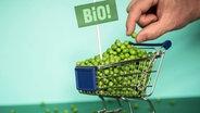 Ein Mini-Einkaufswagen voller Bio-Erbsen aus dem eine Hand eine Erbse entnimmt. © Complize / Photocase Foto: Complize / Photocase