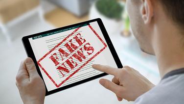 "Mann bekommt auf seinem Tablet die Warnung ""Fake News"" © fotolia Foto: Christian Horz, Stanisic Vladimir"