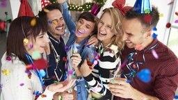 Junge Erwachsene feiern fröhlich mit Sekt und Konfetti Silvester. © fotolia Foto: gpointstudio