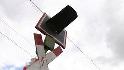 Ein Andreaskreuz mit Ampel ragt in den Himmel.