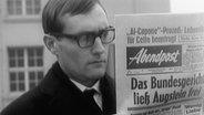 """Rudolf Augstein liest in einer Zeitung mit der Titelstory """"Das Bundesgericht ließ Augstein frei""""."""