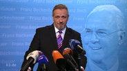 ein Mann vor Mikrophonen, im Hintergrund ein Bild von Beckenbauer