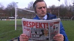 Ein Mann liest in einer Bildzeitung.