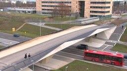 Ein Bus, der unter eine Brücke fährt.