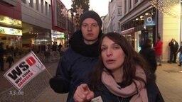 """Zwei junge Menschen in einer Fußgängerzone, der eine hält ein Plakat mit der Aufschrift """"WSD, Wir sind dagegen"""", die andere Person zeigt mit dem Finger in die Kamera."""