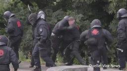 Ein Polizist schlägt auf einen Demonstranten ein.