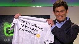 Christian Ehring hält ein T-Shirt mit der Aufschrift: Ich bin nicht arm. Ich bin von der Commerzbank.