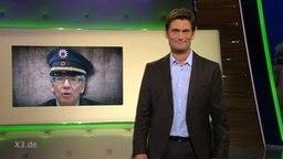 Christian Ehring neben einem Bild von de Maiziere als mit Polizistenmütze.