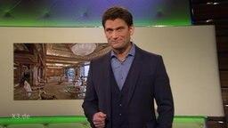 Der Moderator Christian Ehring, im Hintergrund ein Bild von einer Hotellobby.
