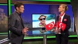 """""""Extra 3""""-Moderator Christian Ehring steht zusammen mit einer Frau an einem Tisch mit Türkeiflaggen."""