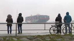 Menschen gucken vom Ufer auf das festgefahrene Container-Schiff.