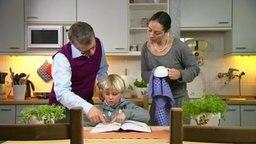 Mutter und Vater helfen einem Jungen bei seinen Hausaufgaben.