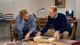 Prinz Harry und Prinz William schauen sich ein Fotoalbum an. © NDR/Oxford Film & Television, honorarfrei