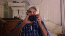 Ein junger Mann hält ein Kameraobjektiv in den Händen und schaut darauf. © NDR/Sulaiman Tadmory