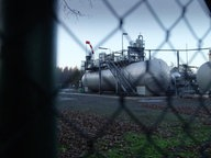 Eine Erdölanlage hinter einem Zaun.