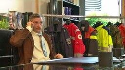 Ein Mann sitzt in einem Büro und telefoniert mit seinem Handy.