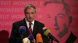 Der Schriftsteller Torsten Sträter vor einem rosafarbenen Plakat, das Klaus Wowereit zeigt.