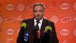 Torsten Sträter am Mikrofon vor einer Wand, die mit Tankstellen-Logos bedruckt ist.