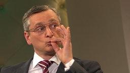Ein Mann mit silberner Brille hält sich die Hand vor den Mund.