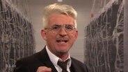 Ein Mann mit weißen Haaren und Brille spricht in die Kamera.