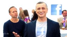 Ein Mann strahlt in die Kamera, ein anderer schaut ihn skeptisch an, im Hintergrund weitere Menschen und ein Face-Book-Symbol.