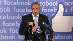 Ein Mann vor Mikrophonen, im Hintergrund das Facebook-Logo.