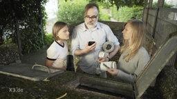 Die Extra3-Familie steht vor den Mülleimern.
