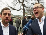 Zwei Männer: Einer mit Mikrophon, einer lacht.