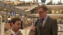 Ein Mann im Anzug wird vor Flughafenschaltern interviewt.