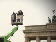 In einem Krankorb stehen drei Menschen, im Hintergrund ist das Brandenburger Tor zu sehen.